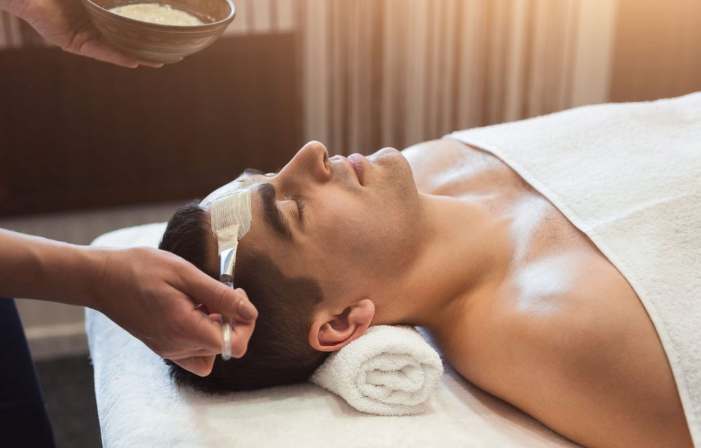 Man getting face mask by beautician at spa