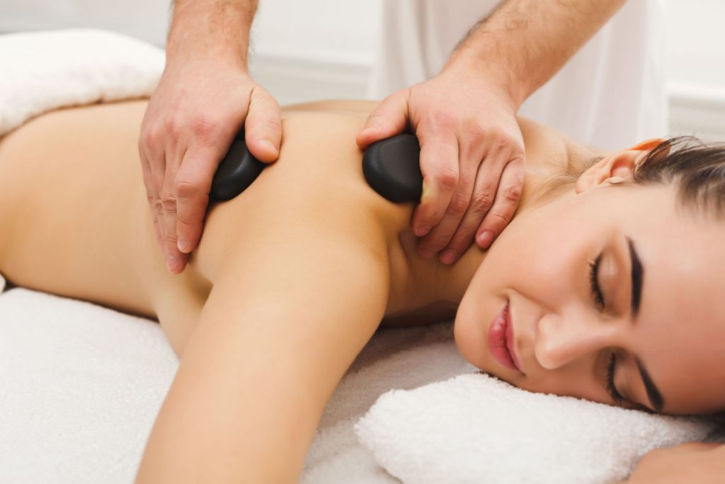 Woman getting hot stones massage at spa salon